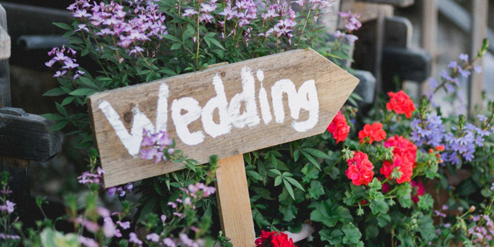 """Ein Holzschild als Pfeil mit der Aufschrift """"Wedding"""", also """"hier gehts zur Hochzeit"""""""